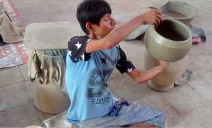 Gerónimo López, alfarero de Simbila, alisando borde de la ceramica
